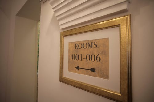 Sign with rooms numbers hanging on white wall in modern hotel