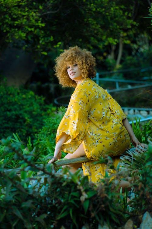 Woman In Yellow Dress Sitting On Handrail