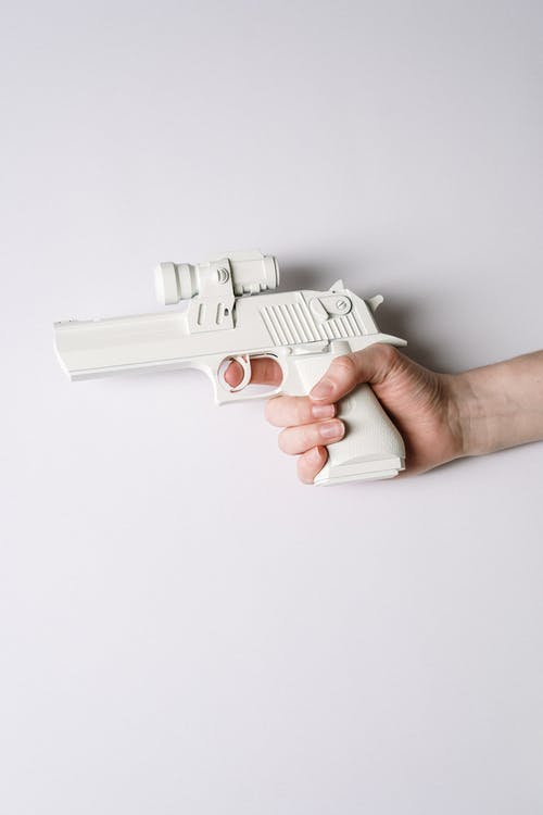 Person Holding White and Gray Semi Automatic Pistol