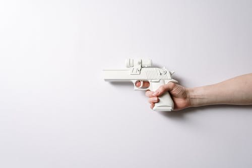 Person Holding White and Gray Toy Gun