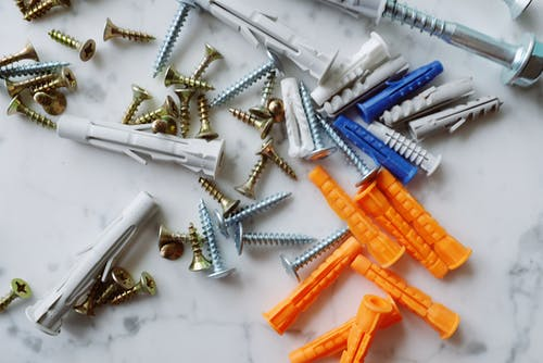 Bunch of plastic multicolored dowels with metal screws placed on white table