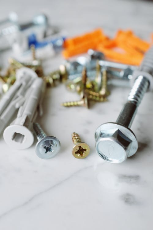 Bunch of various metal screws with multicolored dowels placed on table