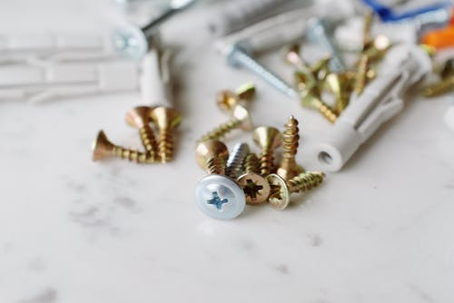 Bunch of various metal screws with plastic dowels placed on white table
