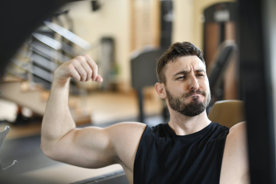 Man In Black Tank Top Flexing His Muscles