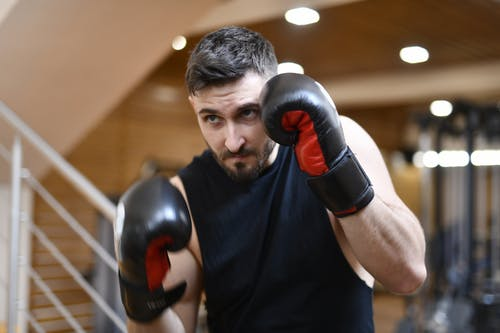 Man In Black Crew Neck Shirt Wearing Black And Red Boxing Gloves