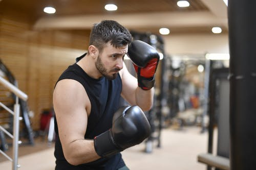 Man in Black Tank Top Wearing Black Boxing Gloves