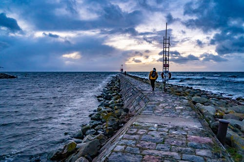 Back view of unrecognizable tourist with backpack walking on stone breakwater against cloudy sunset sky near stormy sea