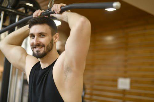 Man In Black Tank Top Holding On Black Exercise Equipment