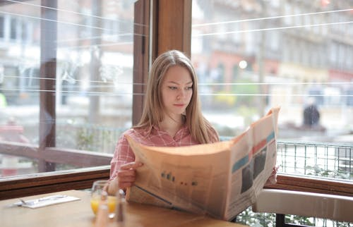 Woman In Pink Long Sleeve Shirt Reading The Newspaper