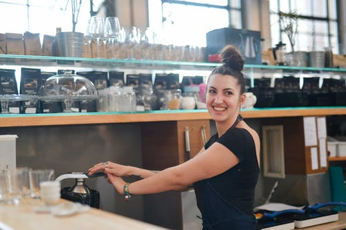 Cheerful female bartender preparing fresh drink in juicer in modern cafe