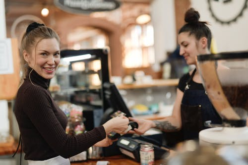 Woman In Black Long Sleeve Shirt Paying At A Cashier