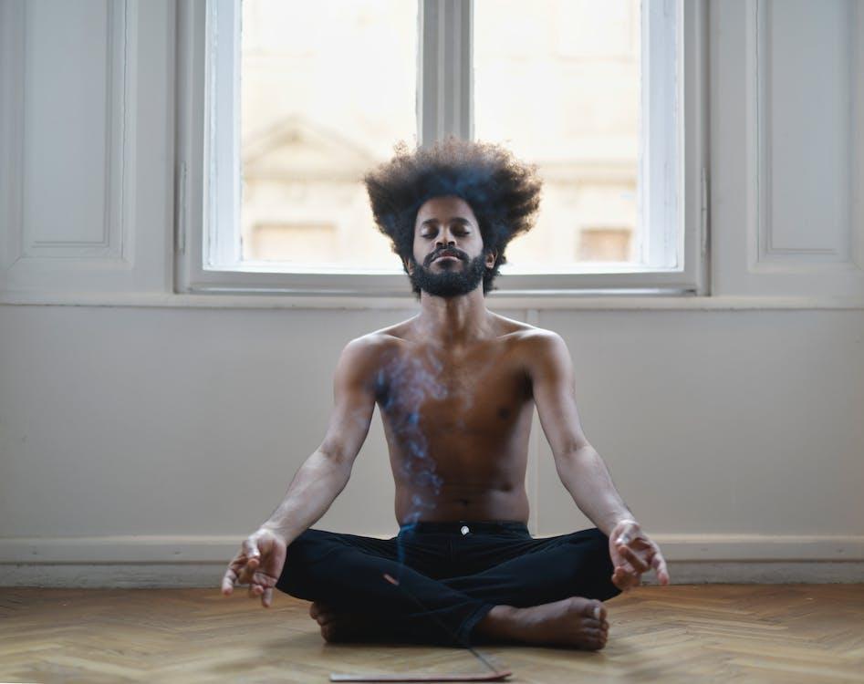 Topless Man In Black Pants Sitting On Brown Wooden Floor