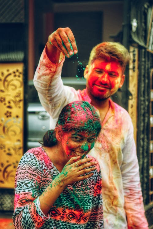 Positive man spilling colorful powder on laughing Indian woman while having fun during Holi festival on town street