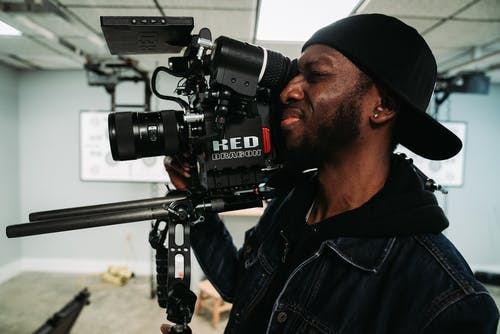 Man in Denim Jacket Holding Black Video Camera
