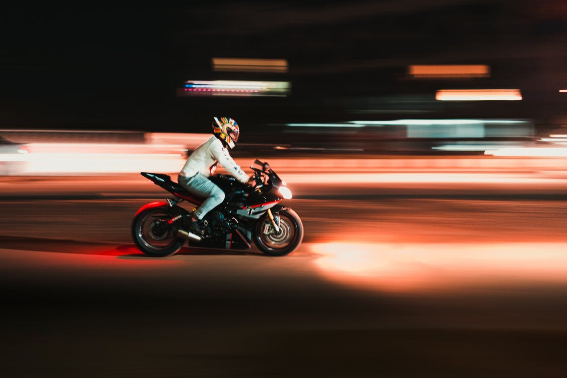 Person Riding Motorcycle in Time Lapse Photography