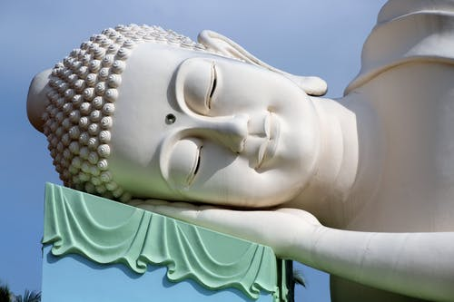 Traditional large sculpture of sleeping Buddha located against cloudless blue sky outside temple