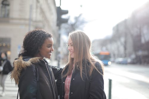 Side view of positive multiethnic young female couple wearing warm coats and standing together on sidewalk and looking at each other while spending time together in city