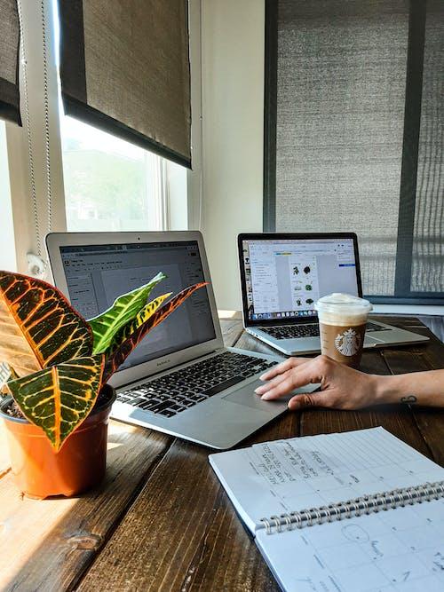在棕色的木桌上使用macbook的人