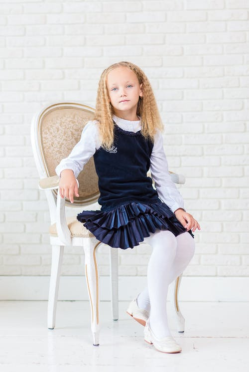 Girl Wearing Blue Dress With White Long Socks Sitting on White Wooden Armchair Beside Wall