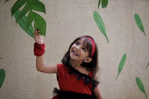 Girl In Red Dress Holding A Leaf