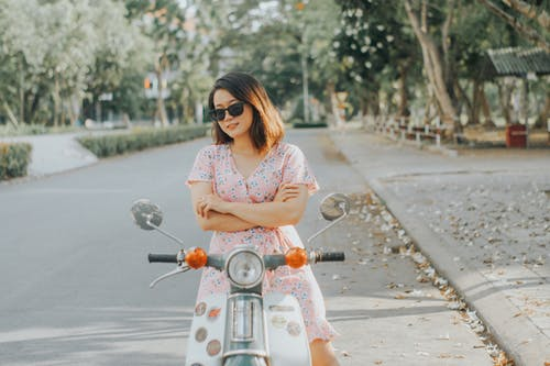 Woman In Pink Floral Dress Riding A Motorcycle
