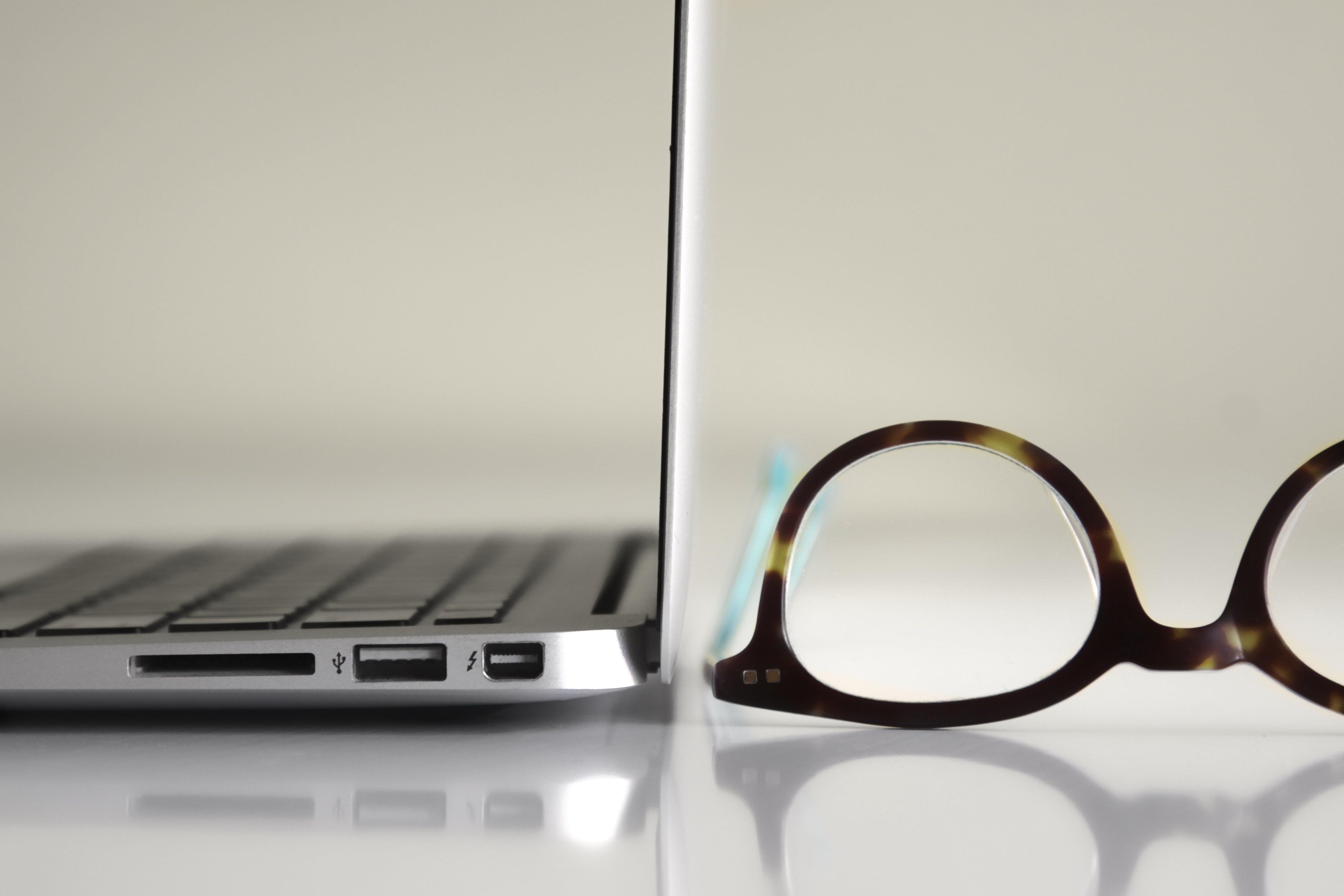 Black Framed Eyeglasses Beside Laptop Computer