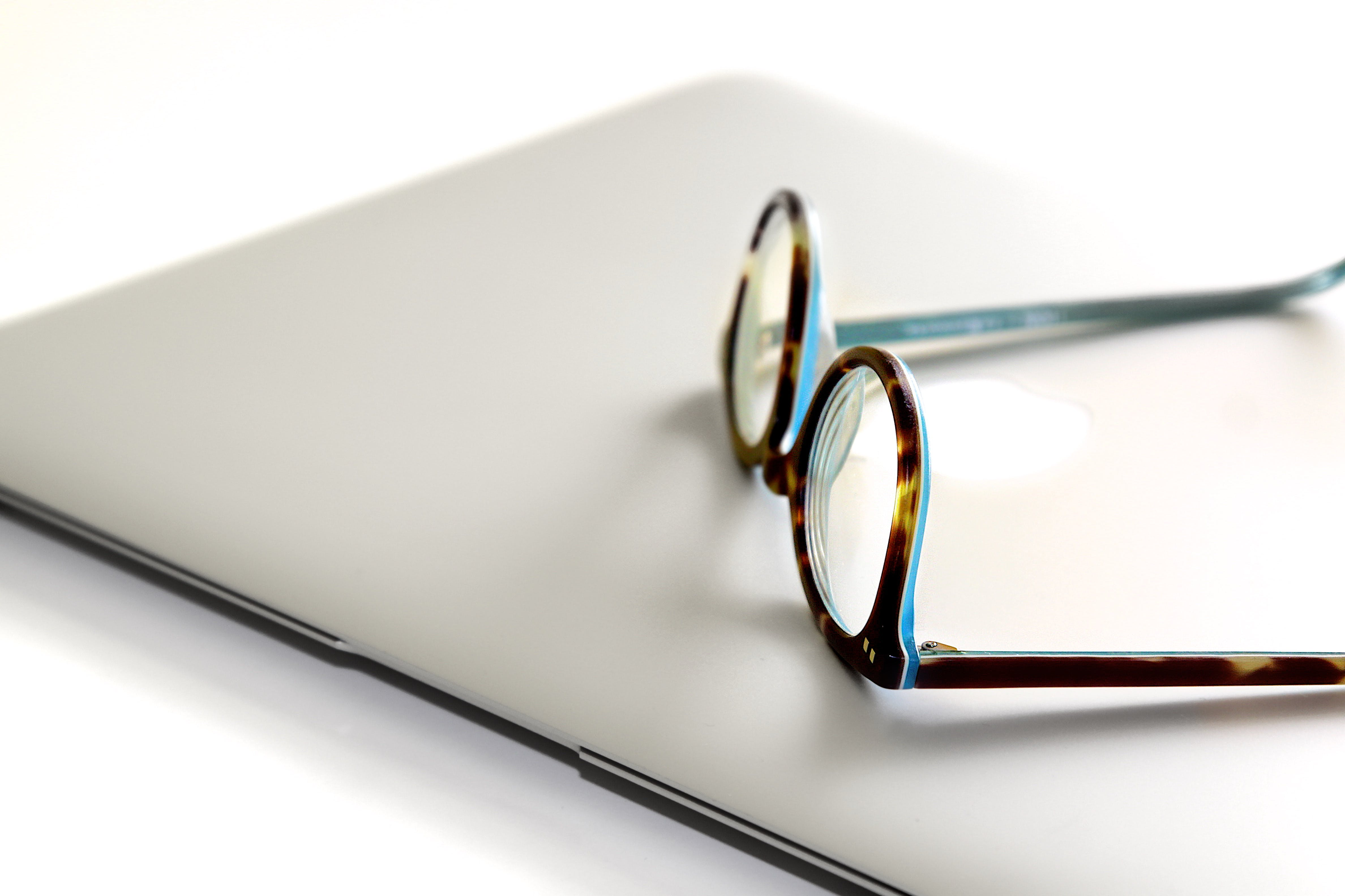 Black and Blue Framed Eyeglasses on Silver Laptop