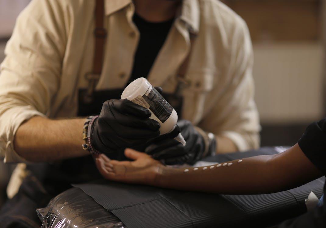 Unrecognizable crop male tattooist preparing arm of client in modern salon
