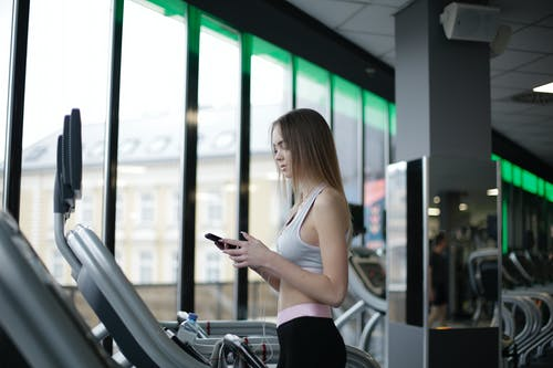 Side view of slim young female athlete in sportswear standing with smartphone and training on treadmill in spacious modern fitness center