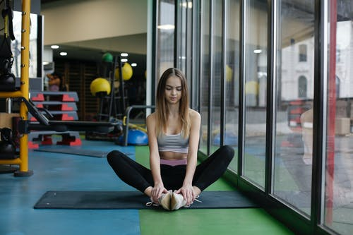Slim young female athlete doing yoga exercise while training in modern gym