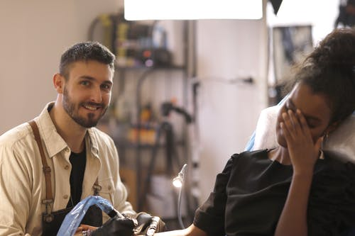 Smiling young bearded tattooist in apron and gloves making tattoo to client in salon