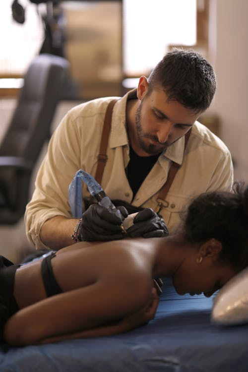 Man in Beige Button Up Shirt Tattooing A Woman On Her Back