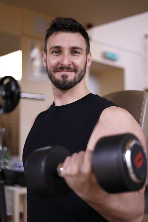 Man in Black Crew Neck T-shirt Holding A Dumbbell