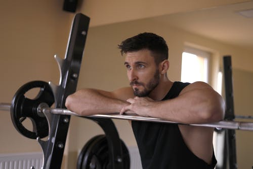 Focused muscular male athlete resting during training in gym