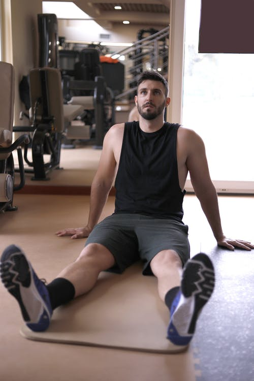 Serious young male athlete resting on mat during training in modern gym