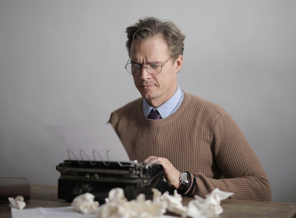 Man In Brown Long Sleeves Using A Typewriter