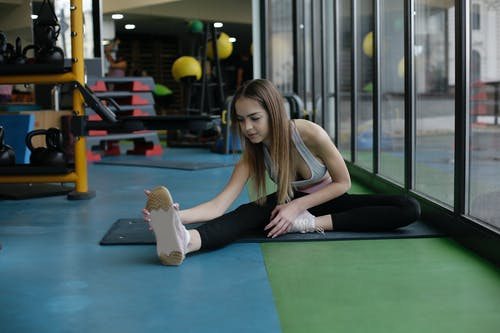 Flexible young sportswoman doing stretching exercise in modern gym