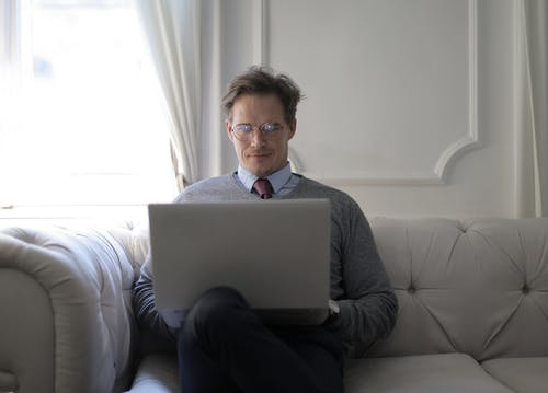 Man In Gray Sweater Sitting On A Couch Using A Laptop