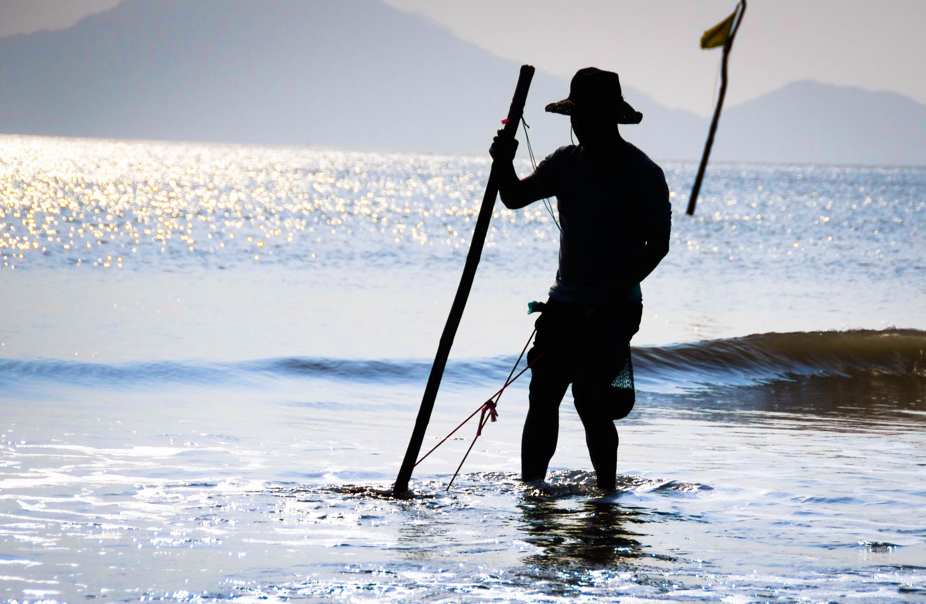 a man using a long stick to fish on the shallow part of the sea