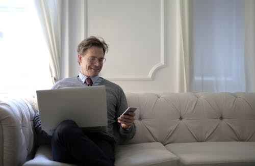 Man With Laptop On His Lap While Using Mobile Phone
