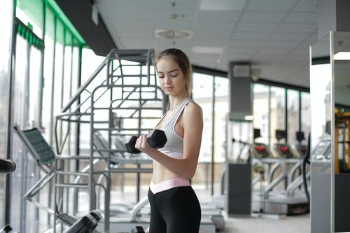 Slim young female athlete exercising with dumbbell in modern gym