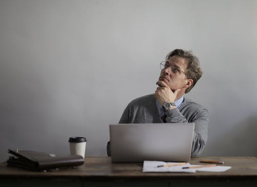 Thoughtful male manager working on laptop in modern workspace