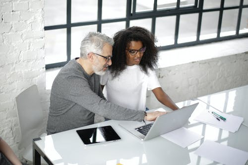 Positive multiracial couple of coworkers using laptop together while working in office