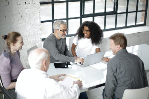 Group of multiracial coworkers gathering around table with gadgets and documents in modern workspace