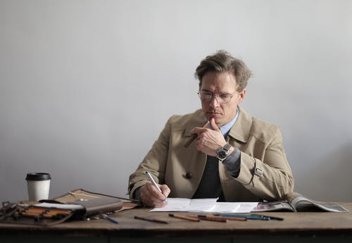 Concentrated male entrepreneur in formal wear eyeglasses and wristwatch holding cigar and writing in papers while drinking takeaway tea in creative studio