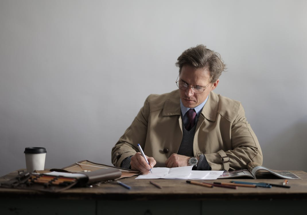 Focused male executive doing paperwork drinking takeaway coffee against gray wall in room