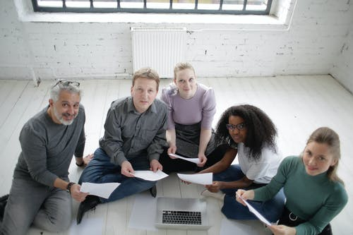 Positive multiracial colleagues working with documents and laptop on floor in modern workspace