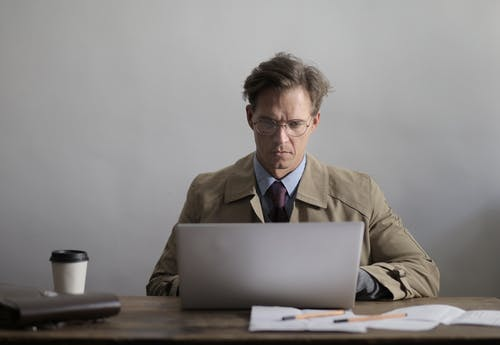 Concentrated man in eyewear working on laptop in light workplace