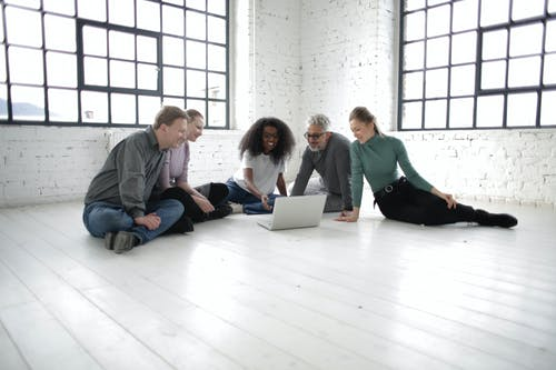 Group of happy multiracial coworkers in casual clothing smiling while watching video on computer gathering on floor in modern workplace