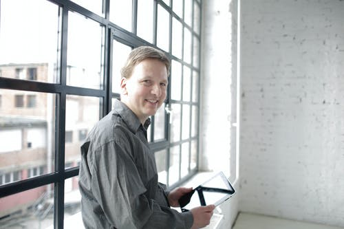 Happy male manager with tablet near window in spacious workspace